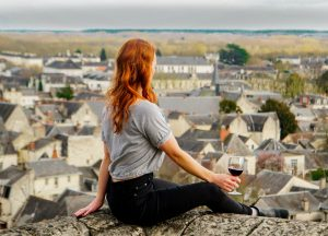 Guide to Loire Valley Wineries, Girl with red hair overlooking chinon with glass of red wine